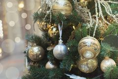 Christmas tree with golden balls and lights with copy space on blurred bokeh background in mall. Close up. Christmas tree with holiday golden balls and lights Royalty Free Stock Photo