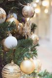 Christmas tree with golden balls and lights with copy space on blurred bokeh background in mall. Close up. Christmas tree with holiday golden balls and lights Stock Images