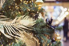Christmas tree with golden decor and lights with copy space on blurred bokeh background in mall. Close up. Abstract Xmas pattern. Royalty Free Stock Photo