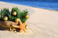 Christmas tree with golden christmas balls and starfish on the s Royalty Free Stock Image
