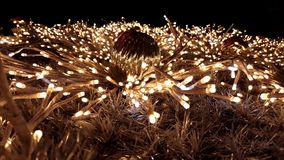 Close shot on a gold tinsel Christmas tree. Christmas tree with golden fairy lights and ornaments. Illuminated New Year tree at night with flashing and shining stock video