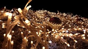 Close shot on a gold tinsel Christmas tree. Christmas tree with golden fairy lights and ornaments. Illuminated New Year tree at night with flashing and shining stock footage