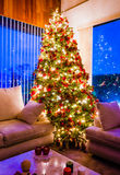 Christmas tree with golden lights in a cozy living room Royalty Free Stock Photo