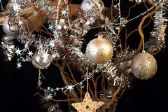 Christmas tree, golden and silver balls, chains and stars on black . Christmas tree with sparkling golden and silver balls, chains and stars on black background Stock Photo