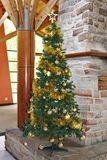 Christmas tree in golden tones. An atmospheric Christmas tree with tinsel and Christmas balls in various gold-colored tones stock photo