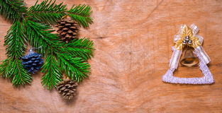 Christmas tree a Green twig and a bell on wooden old rustic back Royalty Free Stock Images