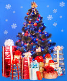 Christmas tree, group gift box. Blue background. Stock Images