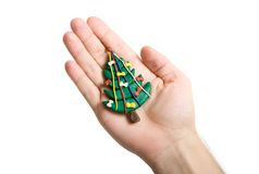 Christmas tree in hand. Plasticine Christmas tree with hand isolated on white stock images
