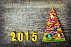 Christmas tree. Handmade knitted Christmas tree with numbers 2015 on old wooden background Royalty Free Stock Photo
