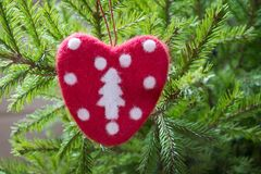 Christmas tree with handmade red felt heart as decor. Xmas card. Close up. Copy space. Winter. Xmas royalty free stock photo