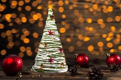 Christmas Tree handmade in rustic style. With red balls and the Golden bokeh royalty free stock photo
