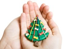Christmas tree in hands. Plasticine Christmas tree in hands isolated on white stock photos