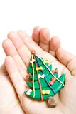 Christmas tree in hands. Plasticine Christmas tree in hands isolated on white royalty free stock images