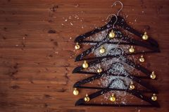 Christmas tree from hangers. Decorated with a gold balls. A concert of Christmas sales. Stock Images
