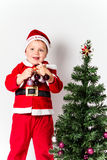 Christmas tree, holding baubles. Baby boy dressed as Santa Claus decorating  Christmas tree, holding baubles. White background Stock Photos