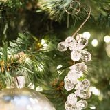 Christmas tree with holiday glass pendant and lights. Close up. Xmas card. Royalty Free Stock Photo