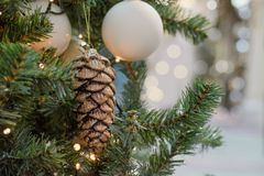 Christmas tree with holiday golden cones and lights with copy space on blurred bokeh background in mall. Xmas card. Stock Photography