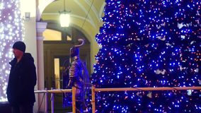 Christmas tree with holiday lights in city. Closeup. A man stands waiting ear the Christmas tree stock video