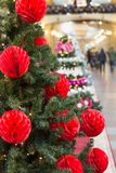 Christmas tree with holiday red balls and lights with copy space on blurred bokeh background in mall. Close up. Christmas tree with holiday red design balls and Royalty Free Stock Images