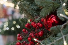 Christmas tree with holly berries as decor and lights with copy space on blurred bokeh background in mall. Close up. Royalty Free Stock Photos