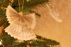 Christmas Tree Impression with Paper Made Angels. Christmas tree closeup with angel ornaments in an Christmassy illuminated home royalty free stock images