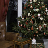 Christmas Tree and Leather Chair. Typical English Domestic Christmas Tree decorated with lights and baubles next to a leather chair with table and a glass of Royalty Free Stock Photography