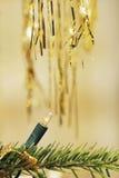 Christmas tree light and gold tinsel Stock Image