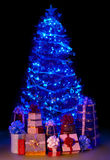 Christmas tree with light and group gift box. Black background Royalty Free Stock Photo