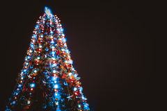 Christmas tree with lights on blue background Royalty Free Stock Image