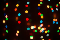 Christmas tree lights in bokeh. On dark background Stock Images