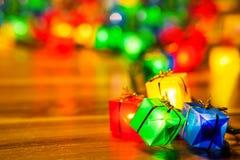 Christmas tree lights bulbs gift box closeup on wooden Royalty Free Stock Image