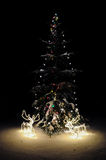 Christmas tree with lights and deers at night. Decorated fur tree for christmas celebration Stock Photos