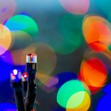 Christmas tree lights of a garland on a blurred background of light spots, close-up. royalty free stock photography