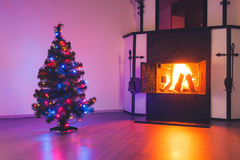 Christmas tree with lights garland and fireplace Royalty Free Stock Image