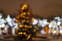 Christmas tree in the lights of illumination in gold tones in defocusing, bokeh. Christmas tree in the lights of illumination in gold tones on the street royalty free stock image