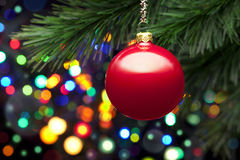 Christmas Tree Lights And Ornament. A red christmas ornament on a tree with many colorful lights with bokeh Royalty Free Stock Images