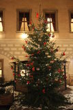 Christmas tree with lights and ornaments. A Christmas tree with lights and ornaments in front of the façade and walls of a historic building in Germany with stock images