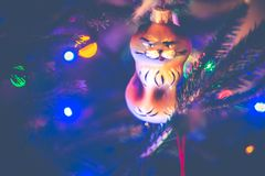 Christmas tree lights and toy cat. Hanging on a festive fir royalty free stock photo