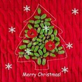 Christmas tree lined with acorns on red background Royalty Free Stock Photo