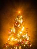 Christmas Tree Lit. On brown wallpaper Stock Images