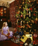 Christmas Tree and Angelic Little Girl. An angelic little girl in a party dress with a pile of Christmas gifts and a large Christmas Tree stock photo