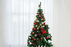 Christmas tree in living room over window curtain stock images