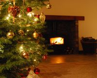 Christmas Tree and log fire. Traditional Christmas tree in front of log fire Stock Image