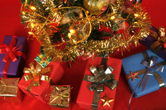 Christmas tree with lots of wrapped gifts. A colorful Christmas tree with lots of shiny wrapped gifts, beautiful ornaments and  sparkling lights, horizontal Royalty Free Stock Photo