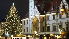 Christmas tree luminous and shines beautiful decorated with golden ornaments and flasks, historical architectural city. Olomouc with Gothic town hall with stock video