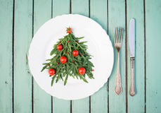 Christmas tree made of arugula and cherry tomatoes on white plat stock photography