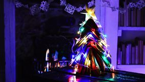Christmas tree made from books with fire and lights. Christmas tree made from books. Night scene of dark room in home illuminated with fairy lights in front of stock video footage