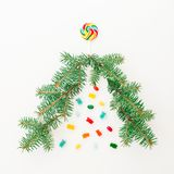 Christmas tree made of branch of winter tree and bright candy on white background. Holiday concept. Flat lay, top view copy space. Christmas tree made of branch stock photography