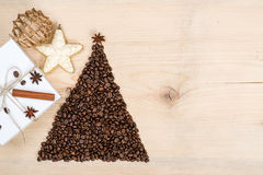 Christmas tree made from coffee beans and gift box on wooden bac. Christmas tree made from coffee beans and gift box on the wooden background. Top view, copy Stock Image