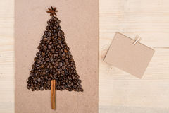 Christmas tree made from coffee beans and paper card on wooden background. Top view, copy space.Winter holidays concept. Royalty Free Stock Photography